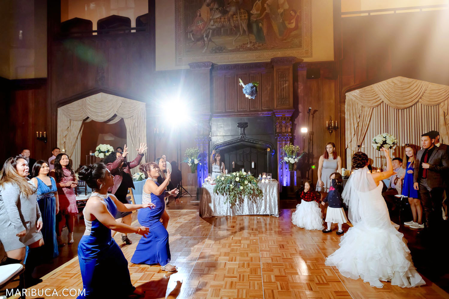 The bride tosses wedding bouquet to friends and bridesmaids in the Great Hall, Kohl Mansion, Burlingame