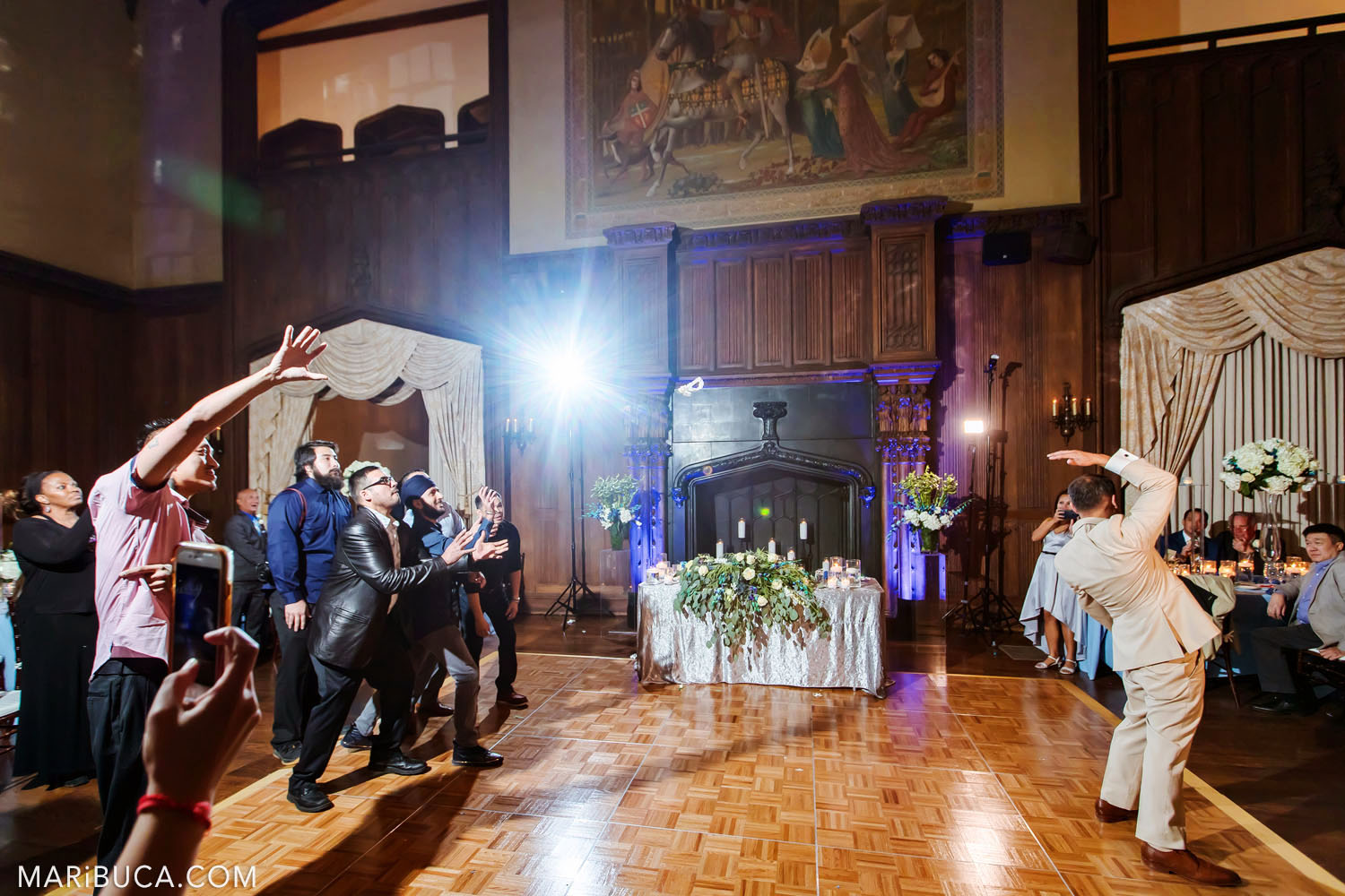 The groom tosses wedding bouquet to friends in the Great Hall, Kohl Mansion, Burlingame