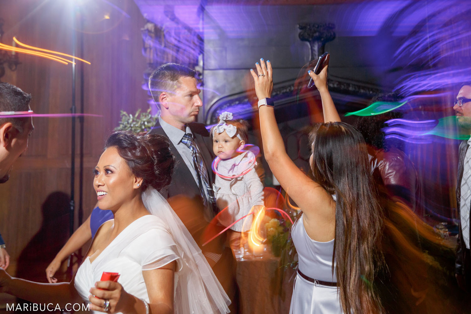 The bride and guests are dancing during the wedding reception in the Great Hall, Kohl Mansion, Burlingame