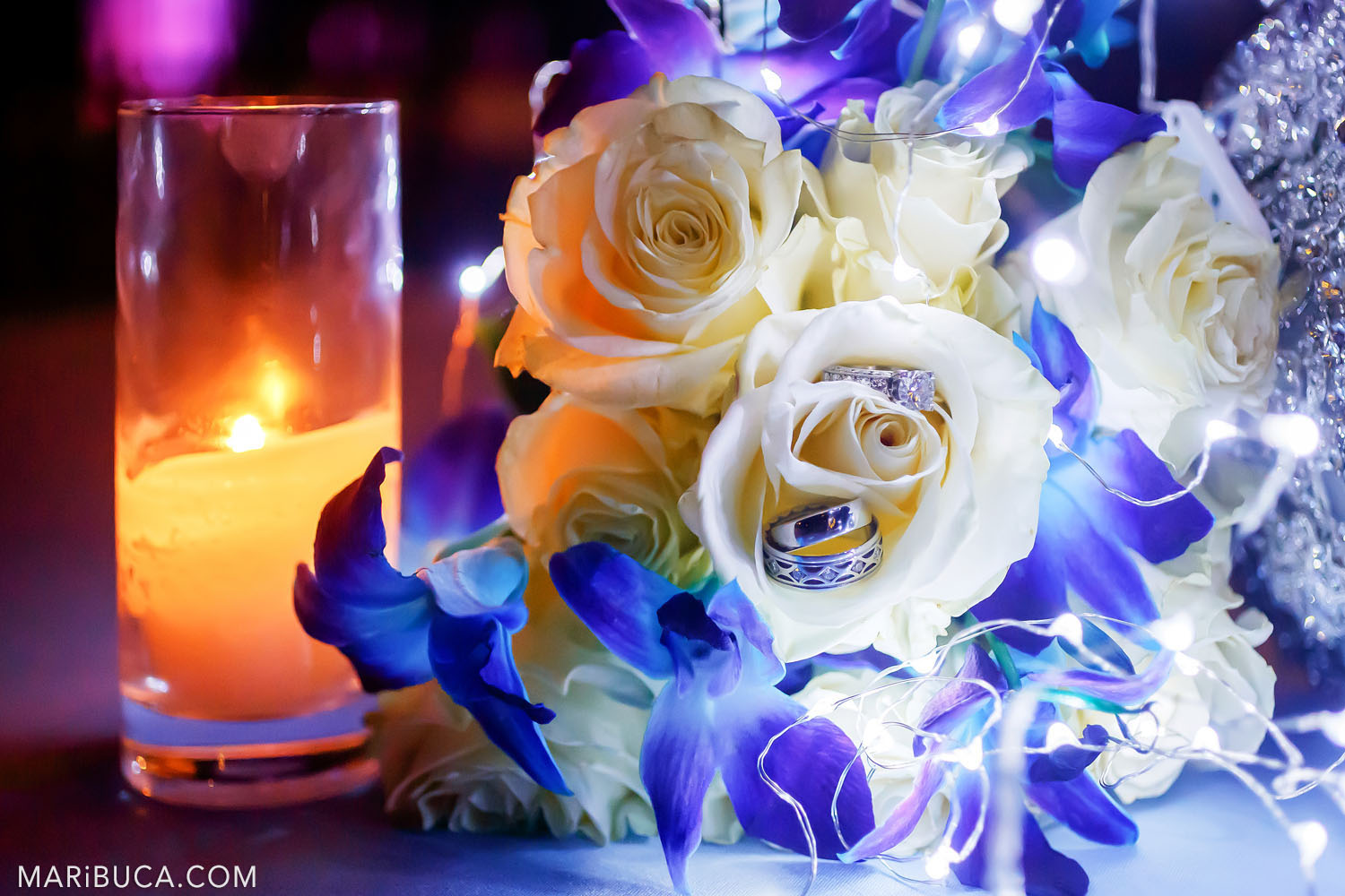 Wedding and engagement rings and engagement ring lie inside a rose flower surrounded orange candle in the glass and white roses and navy flowers.