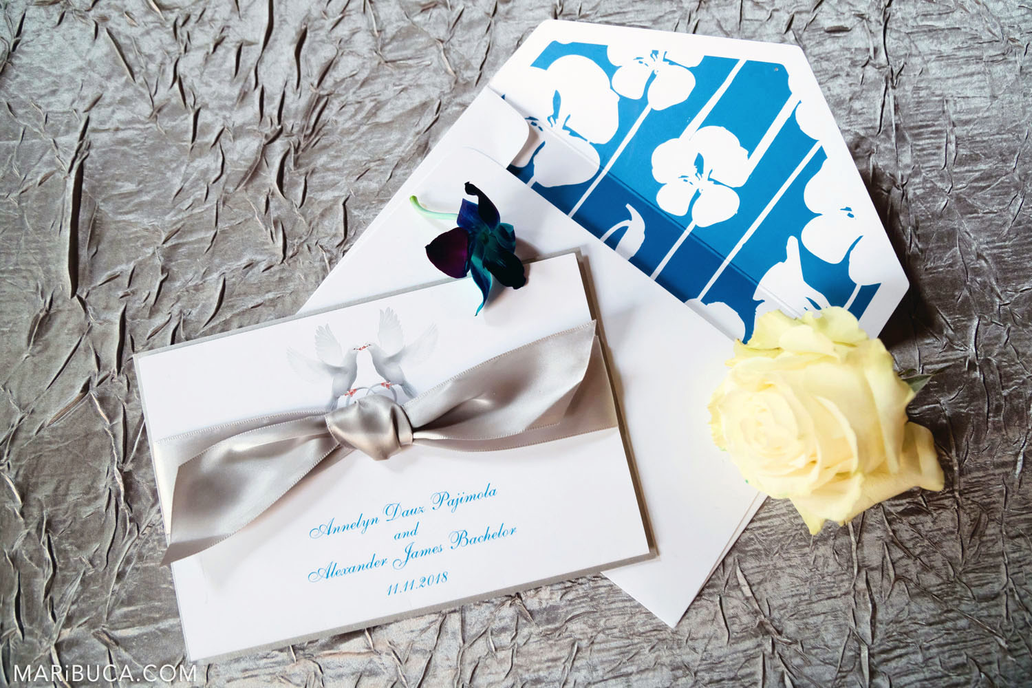 Wedding invitations: white envelopes with silver bow, yellow rose and silver background