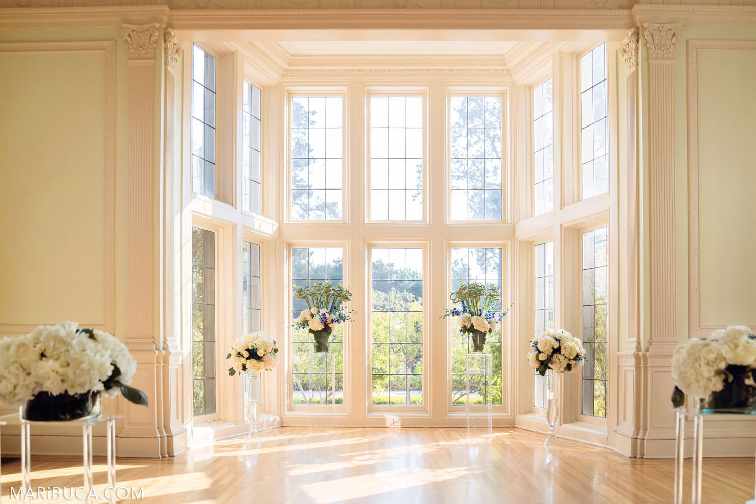 the white hall for the wedding ceremony is decorated with white flowers in the Dining room, Kohl Mansion, Burlingame
