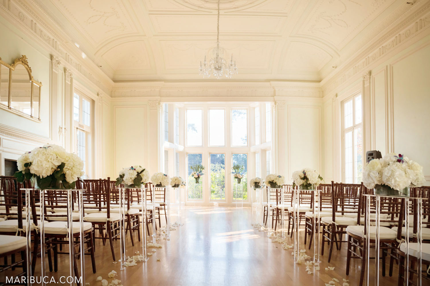 Wedding ceremony decoration such as with white flowers stand in the high vases and big light windows and ceilings in the sunny day, Dining room, Kohl Mansion, Burlingame