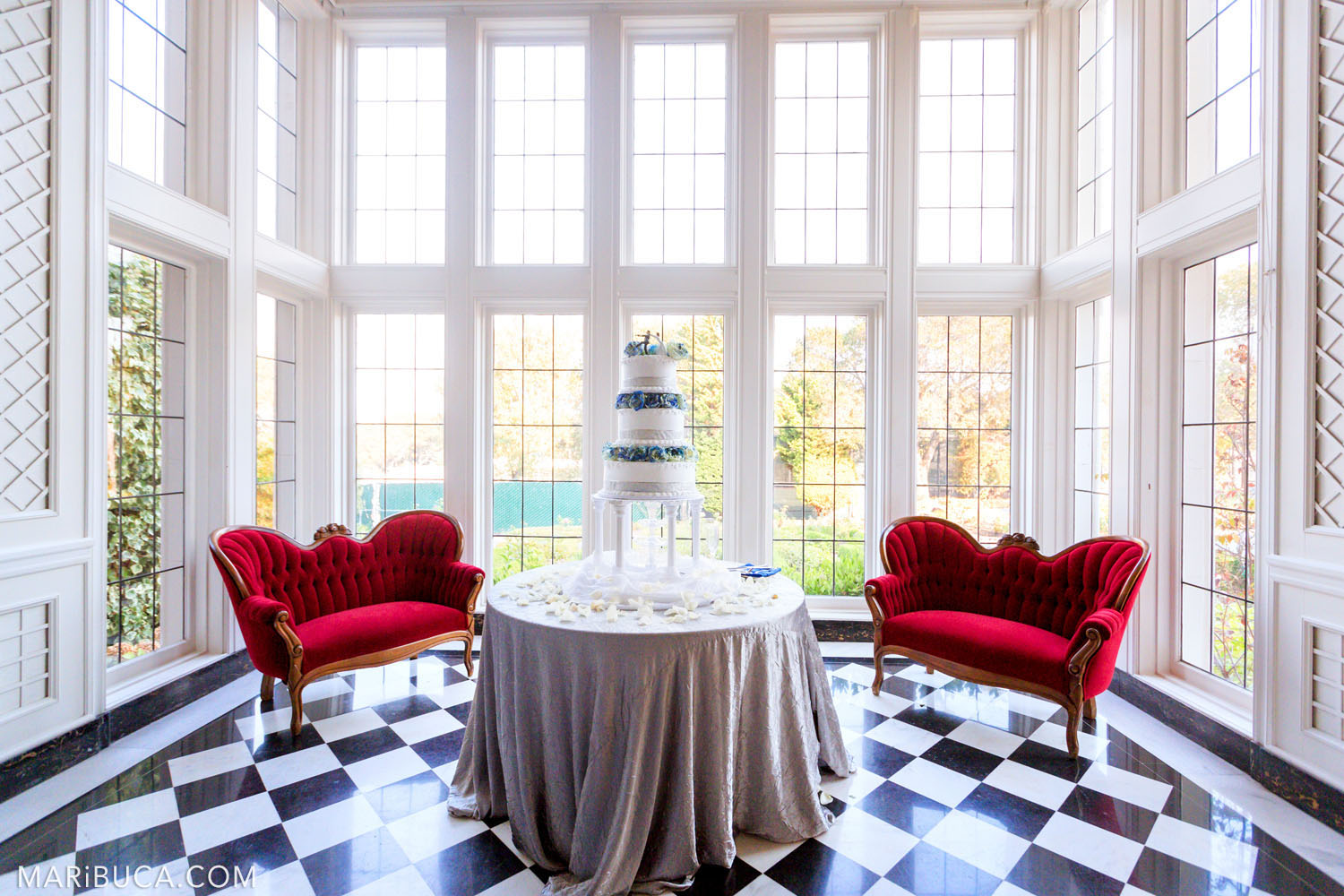 Wedding decorations in the middle of the white room are two red sofas on opposite sides, in the center is a round table with a silver tablecloth and a three-story white with blue cake in the Morning Room, Kohl Mansion, Burlingame