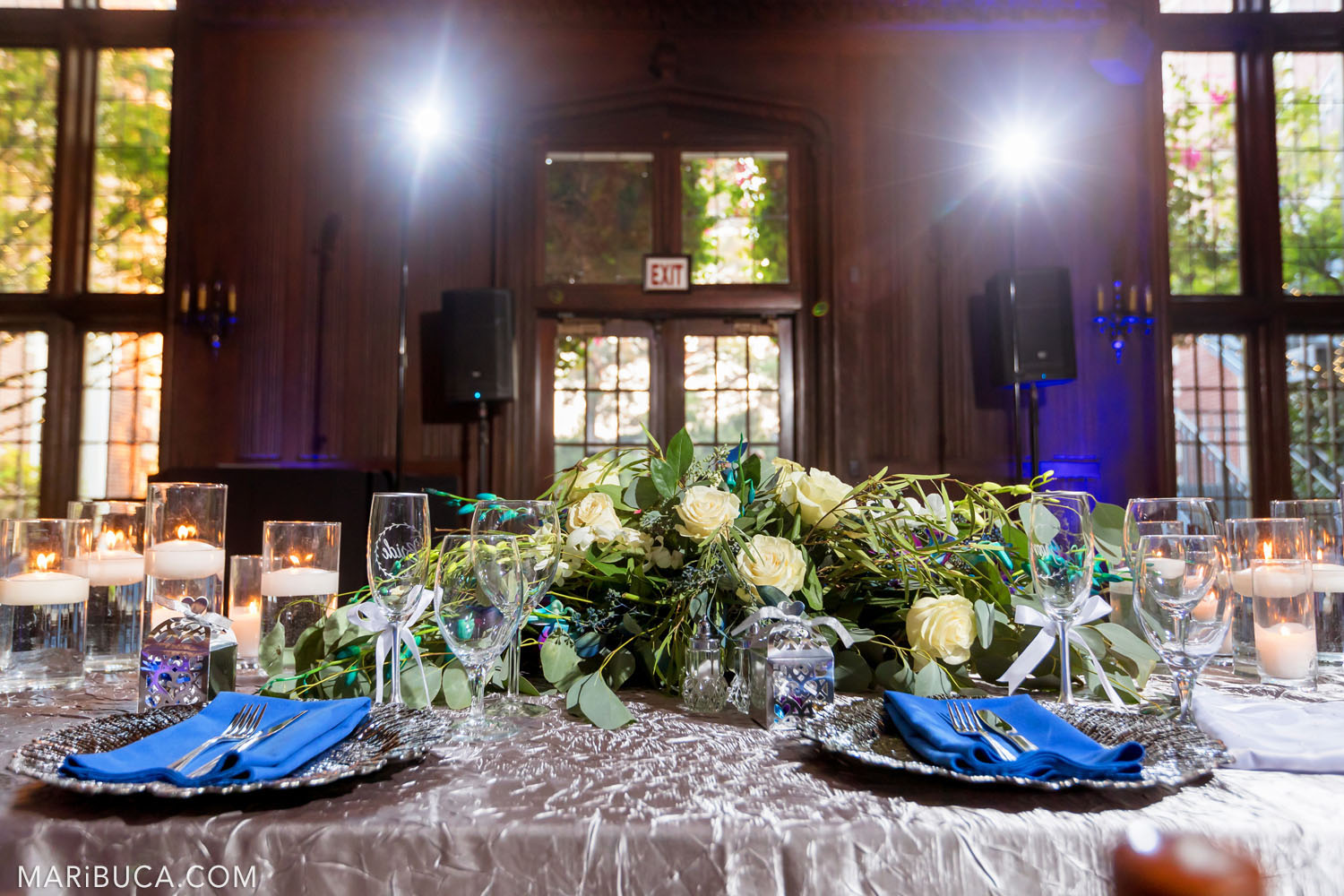 Wedding decoration: newlyweds coupe table with big decoration fresh white roses bouquet, glasses, lit candles in the glasses with water and lights as background in the Great Hall, Kohl Mansion, Burlingame
