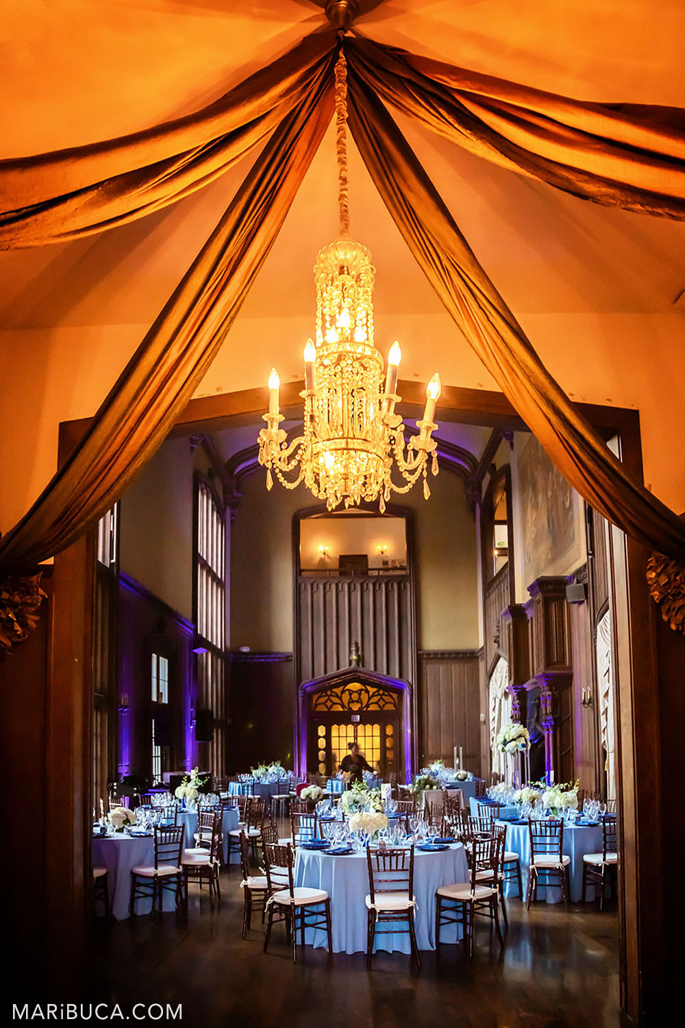 with blue round tables, high ceilings and purple lights in the background. In the foreground, the hall is decorated with an openwork chandelier with candelabra in orange lighting in the Great Hall, Kohl Mansion, Burlingame