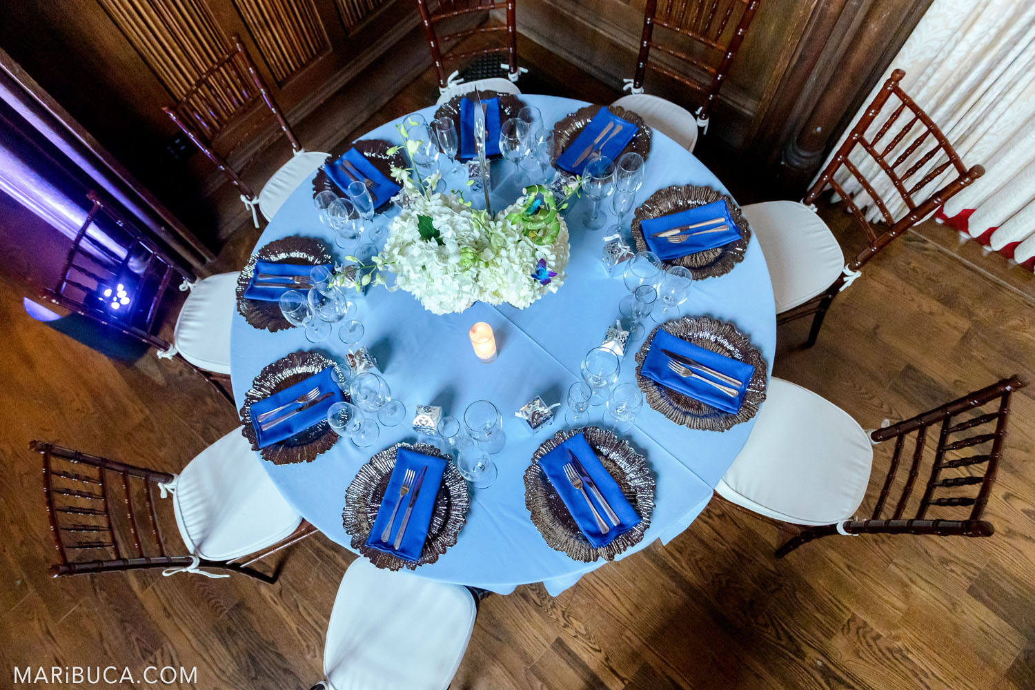 Rounded light blue table with navy blue towels and white fresh flowers in the Great Hall, Kohl Mansion, Burlingame