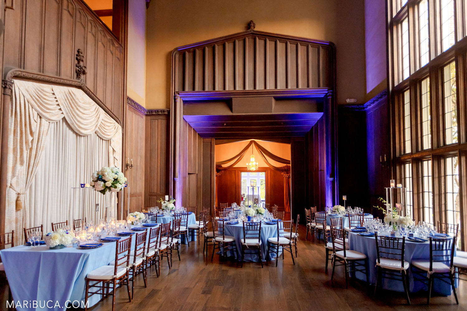 beautiful wooden room with a beige curtain and light blue tables decorated for a wedding in the Great Hall, Kohl Mansion, Burlingame background of purple and orange tones of the wedding theme
