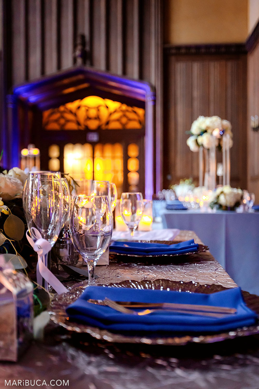 table decoration for the bride and groom: blue napkins lie on plates, newlywed glasses on the background of orange and purple light Great Hall, Kohl Mansion, Burlingame