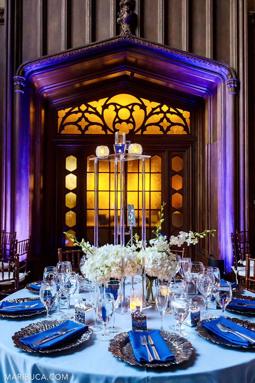 Wedding decoration of the Great Hall with brown walls and purple-orange lights and part of light blue round table and white flowers in the Kohl Mansion, Burlingame