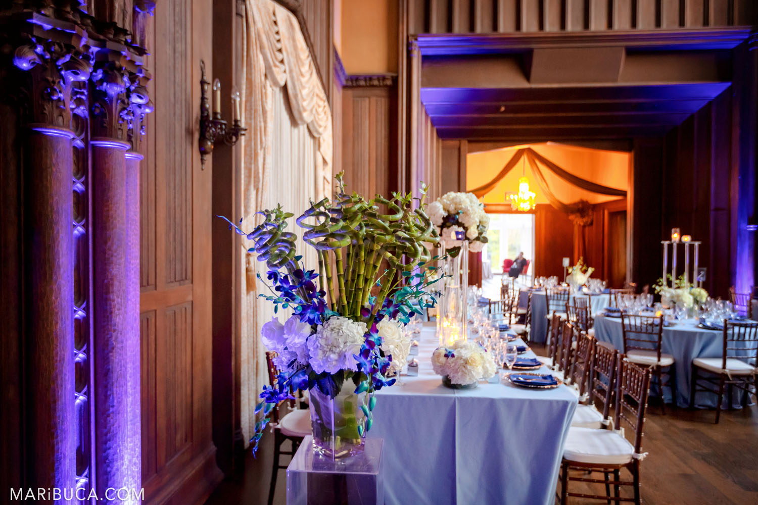 Wedding decoration of the Great Hall such as light blue tablecloths, flowers and an amazing purple lights in the Kohl Mansion, Burlingame
