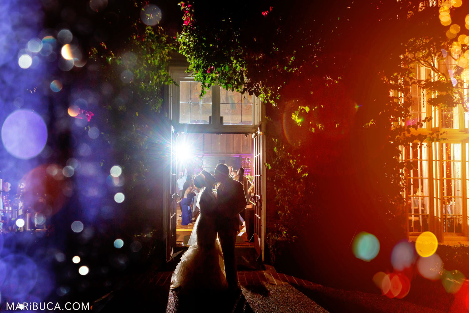bride and groom on the background of Grand Hall and dancing guests, surrounded by purple-orange light and multicolored bokeh during night time wedding in the Kohl Mansion, Burlingame