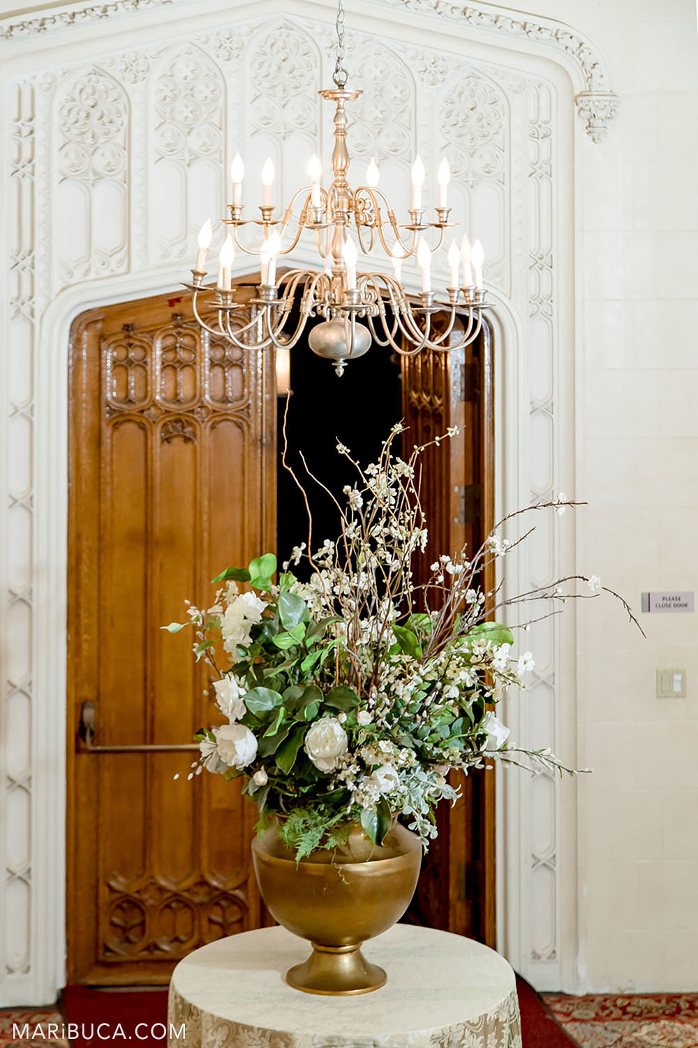 Entry Hall has beautiful white walls, big white flowers and chandelier, Kohl Mansion, Burlingame