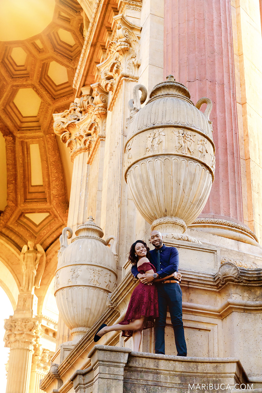 Fiance and fiancee hug each other and stand in the stairs of the San Francisco Palace of Fine Art