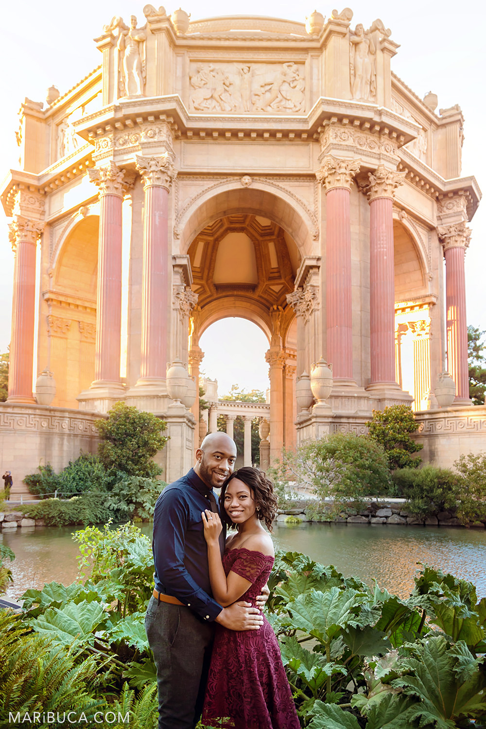 Lovely couple hug and smile in the Palace of Fine Art, San Francisco.