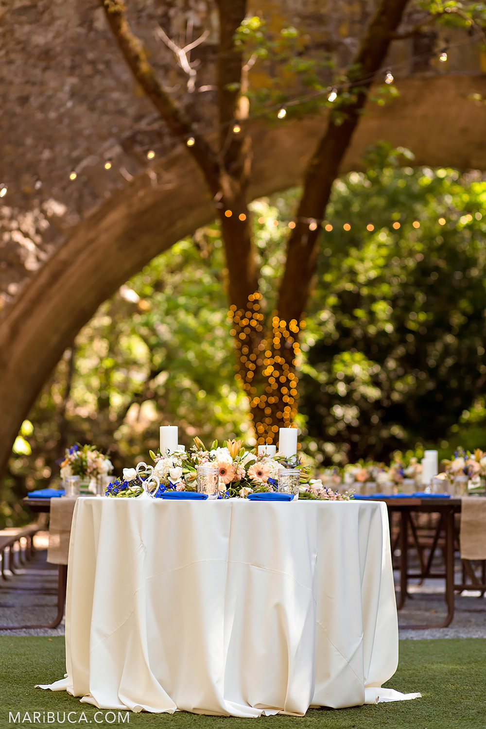 Wedding table decorations surrounded the guests tables and orange light element in the background in the Saratoga Springs Venue