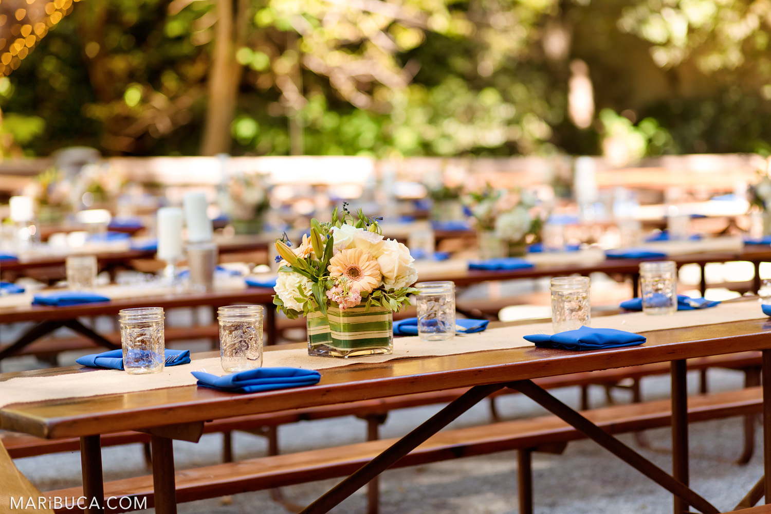 Wedding tables decoration: flowers in the vases, navy blue napkins, and glasses of water in the Saratoga Springs Venue