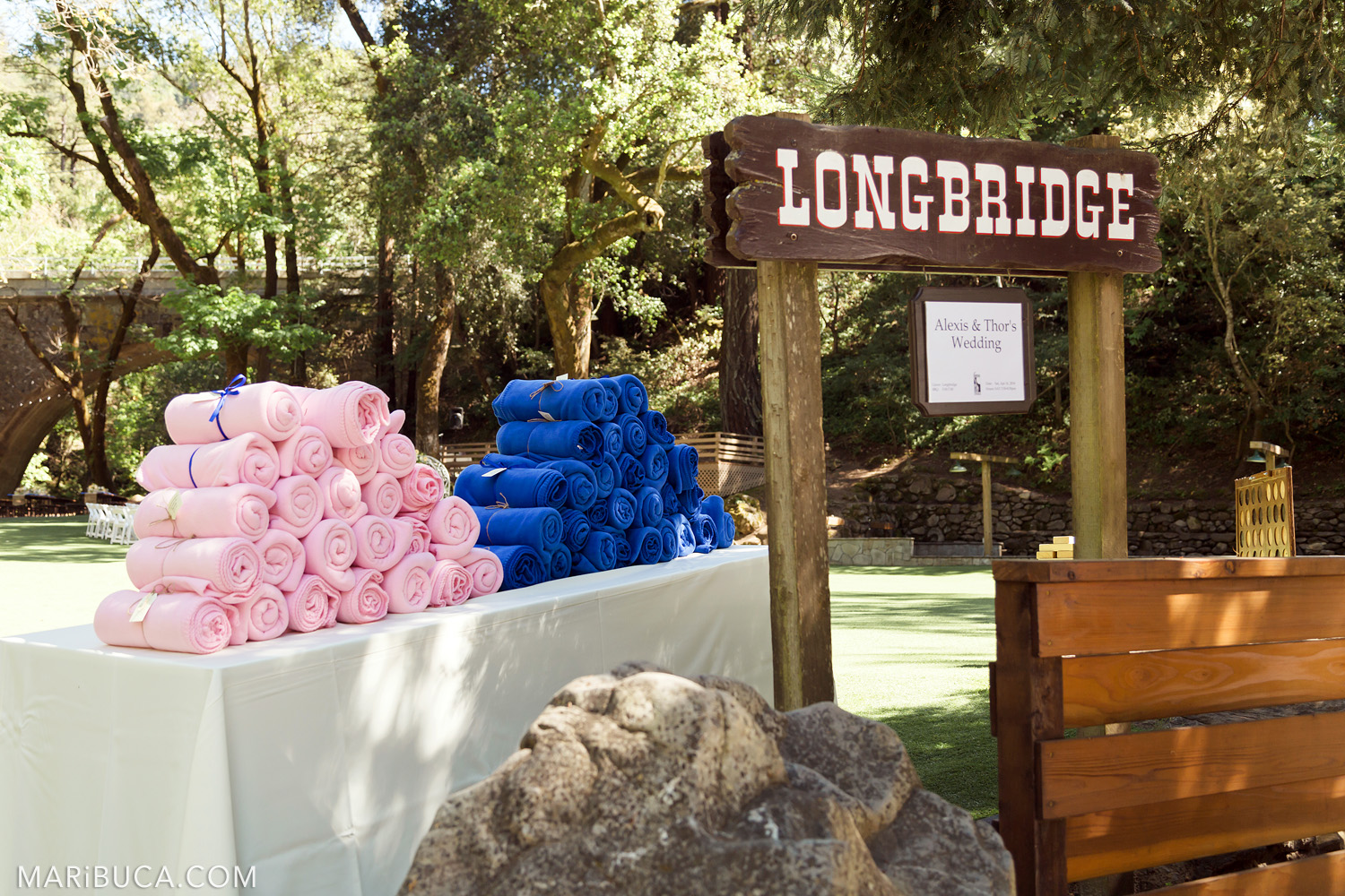 Longbridge brown wooden sign, light pink and navy blue blankets for the guests in the in the Saratoga Springs Wedding.