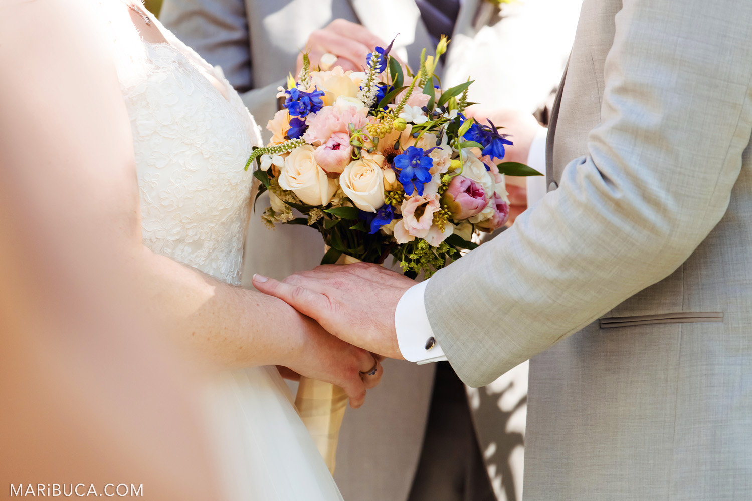 The groom holds bride's hand during the wedding ceremony and the bride holds her colorful wedding bouquet in the in the Saratoga Springs Venue