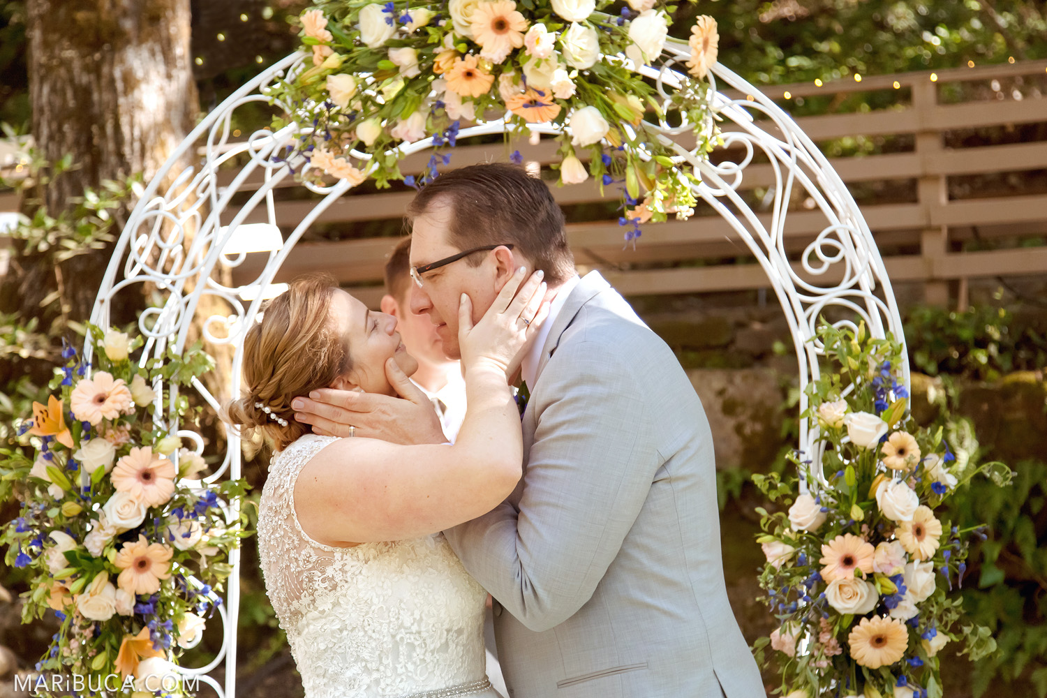 First kiss the bride and groom as newlyweds couple surrounded white arch and fresh light orange flowers in the Saratoga Springs Wedding.