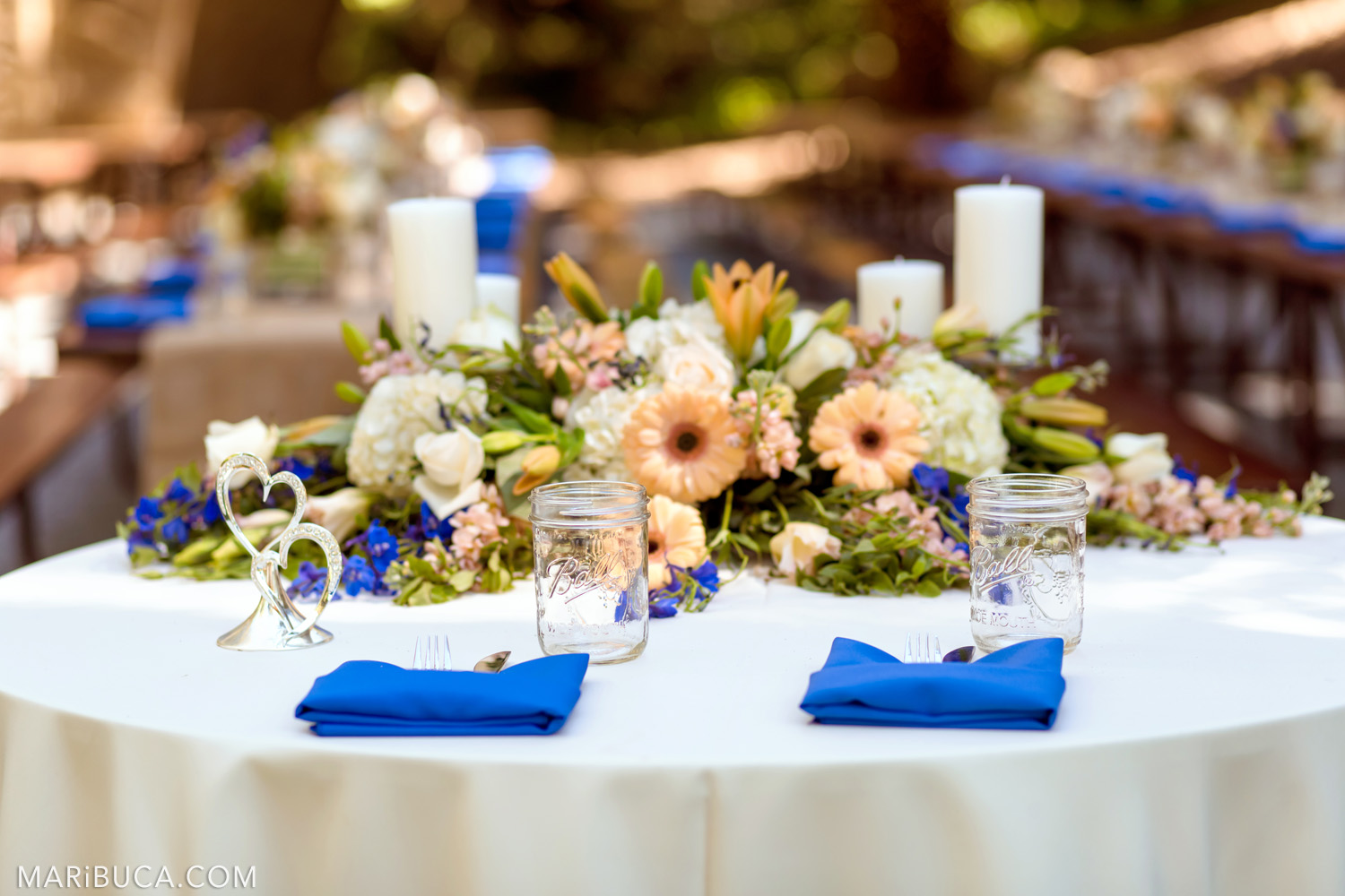 Wedding decoration of tables with white tablecloths, navy blue napkins, white candles in the Saratoga Springs Wedding