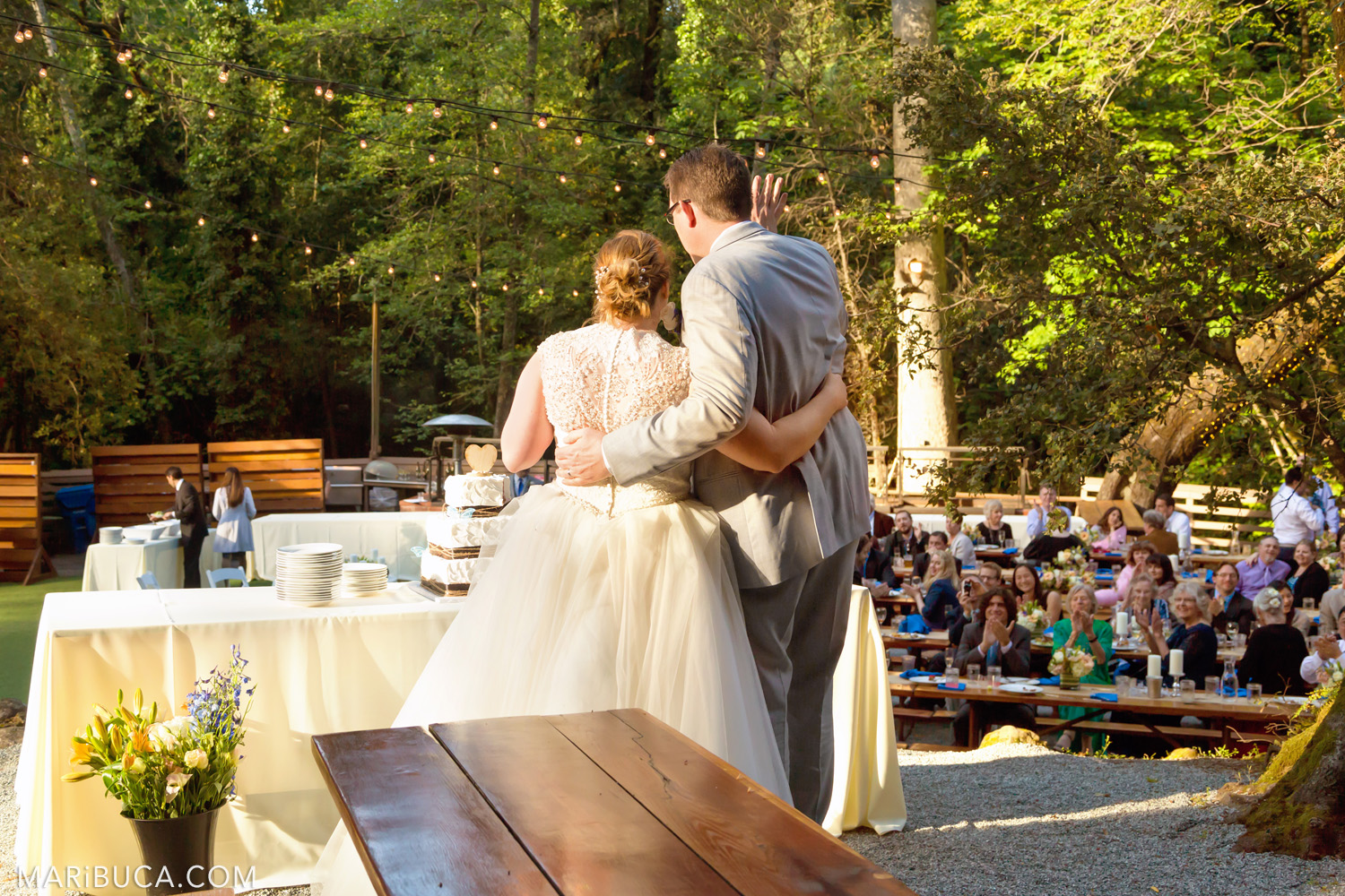 Bride and groom face guests before cutting the wedding cake in the Saratoga Springs Wedding
