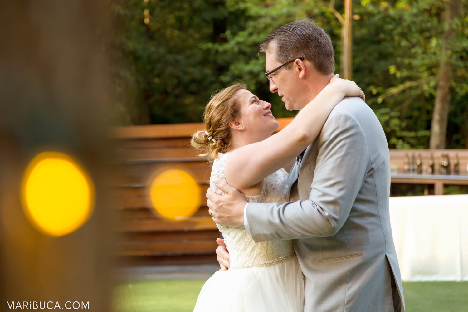 The bride and groom look each other during the first dance and surrounded orange lights in the Saratoga Springs Wedding