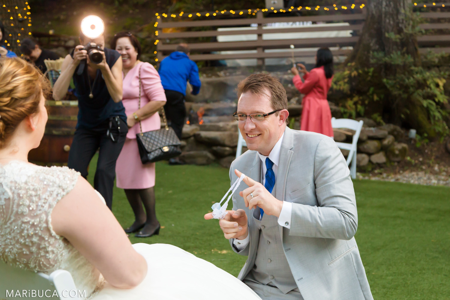 The groom shows bride's garter in the Saratoga Springs Wedding