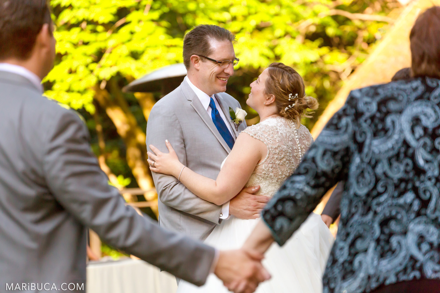 The groom and bride smile each other surrounded the guests in the Saratoga Springs Wedding