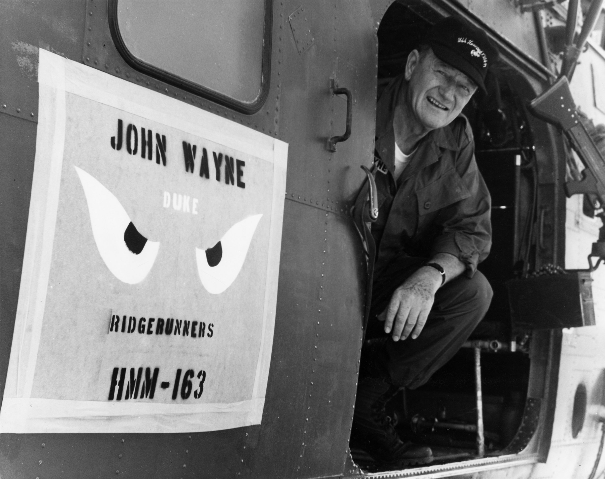 """John Wayne aboard the Medium Lift Tiltrotor Squadron HMM-163 while visiting the troops in Vietnam in 1966. The aircraft was commandeered by the US Marine Corps helicopter squadron known as the """"Ridge Runner's"""". The HMM-163 featured painted """"Genie Eyes"""" after the """"I Dream of Jeannie"""" TV show on the side of the helicopter. Photo courtesy of CPL. L. L. Atherton"""
