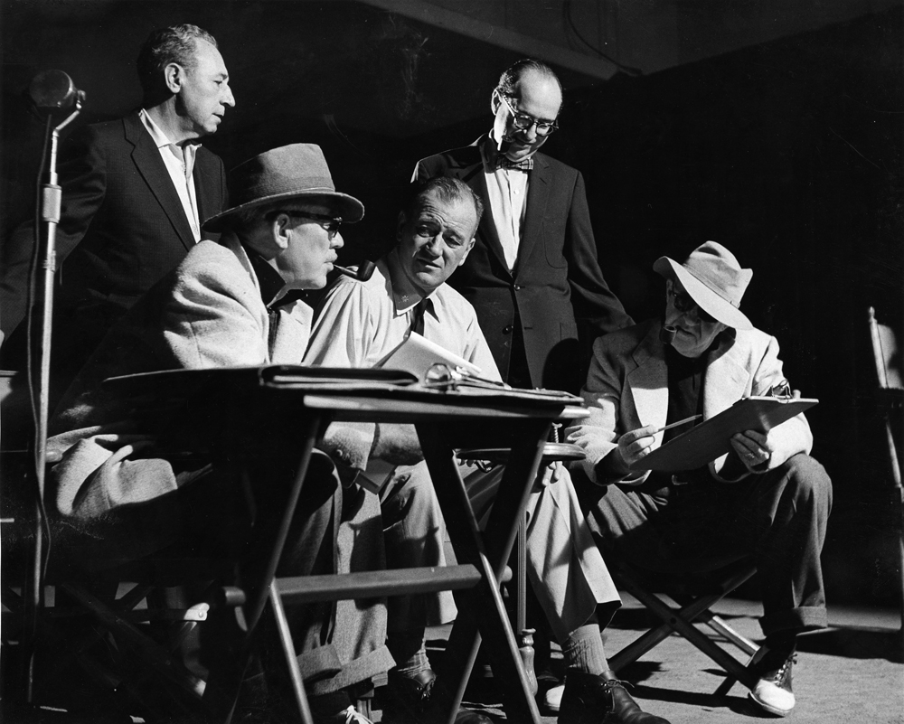 Seated from left- Ward Bond, John Wayne, and John Ford behind-the-scenes of  The Wings of Eagles  (1957), photo courtesy of MGM