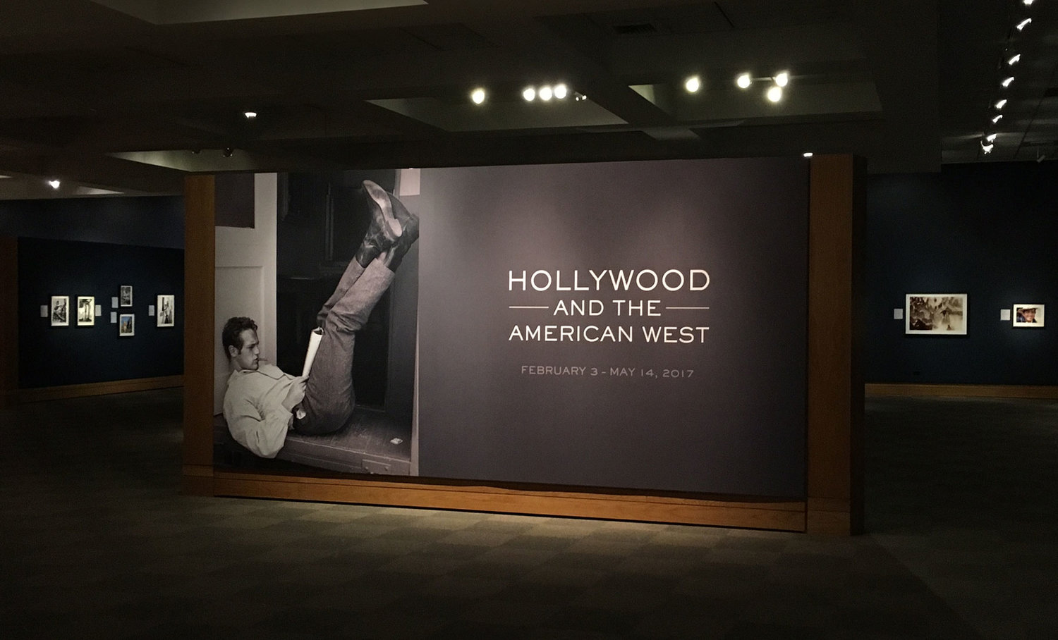 The entrance to the exhibit features an image of Paul Newman reading the script for  The Left Handed Gun  (1958) in front of his dressing room on the Warner Bros. lot in Burbank, California. Photo courtesy of John Wayne Enterprises