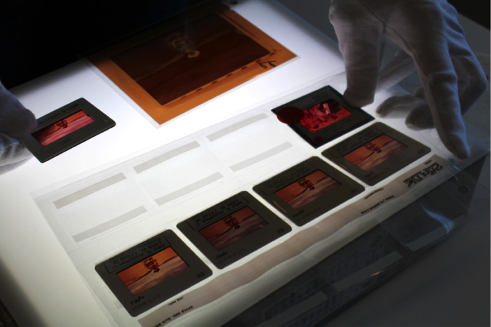 Original slides featuring John Wayne on the set of  The Searchers  (1956) are viewed using a lightbox. Photo courtesy of John Wayne Enterprises