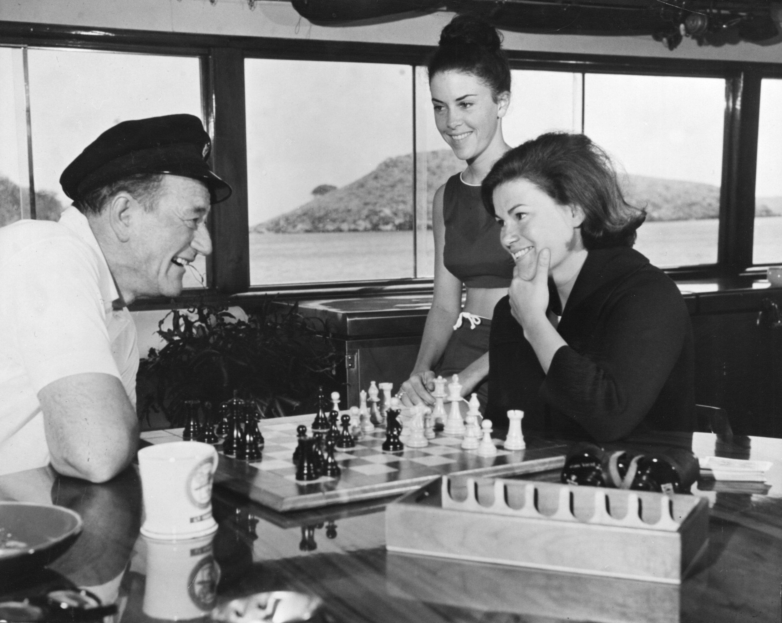 John Wayne with his daughter Melinda aboard  Wild Goose  enjoying a game of chess.