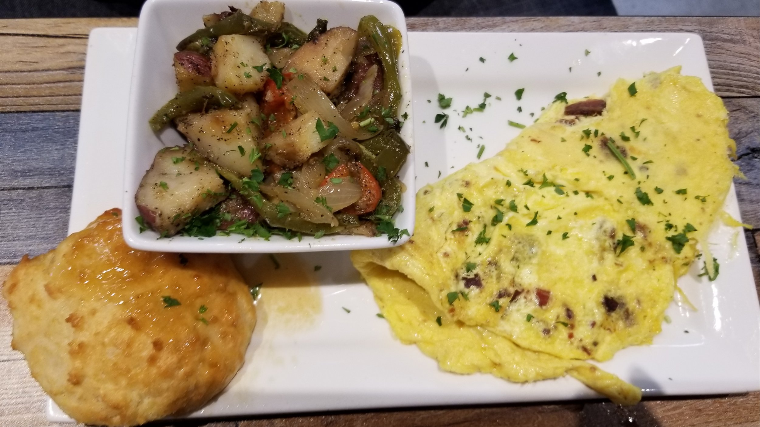 MEAT LOVER OMELETTE- $13.95  Bacon Omelet with breakfast potatoes, and a biscuit.