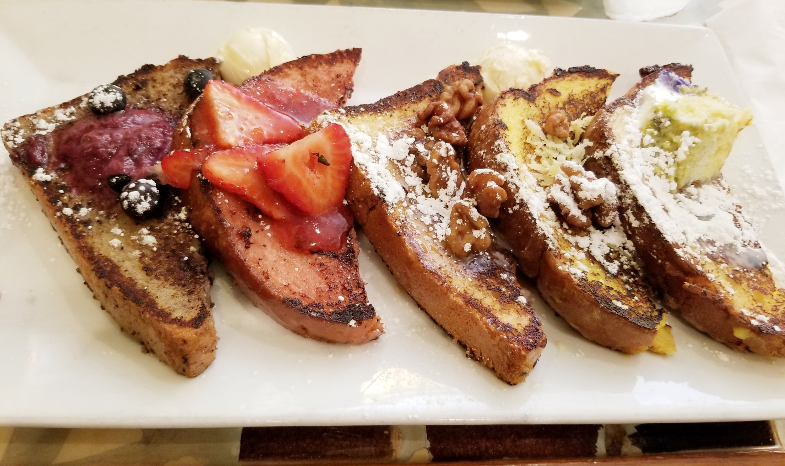 "The World Famous "" French Toast Flight""  Strawberry, Blueberry, lemon, and caramel French toast. $11.75"