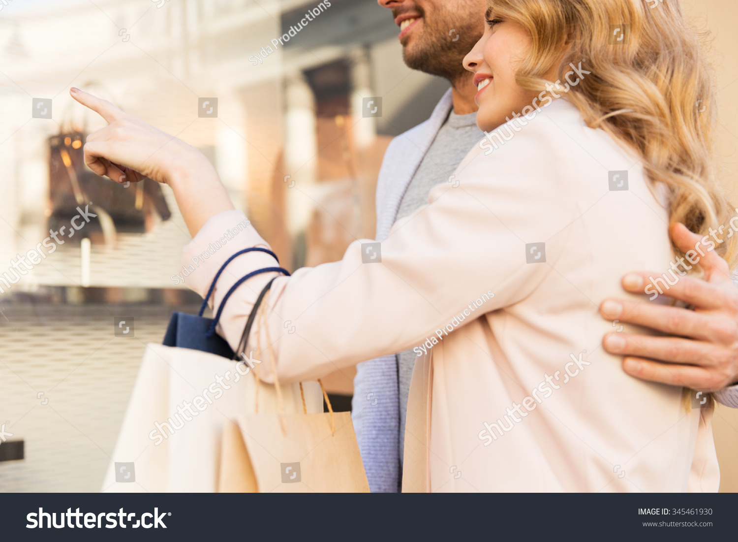 stock-photo-sale-consumerism-and-people-concept-close-up-of-happy-couple-with-shopping-bags-looking-at-shop-345461930.jpg