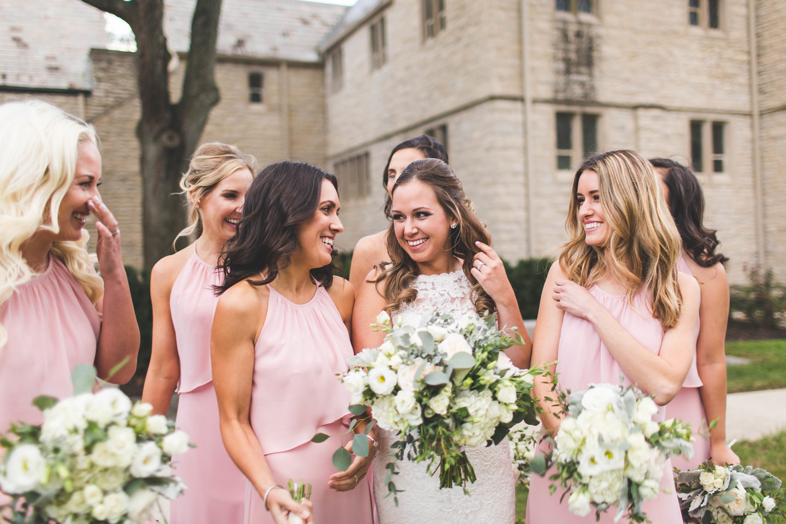 bride and bridesmaids laughing with flowers outside church