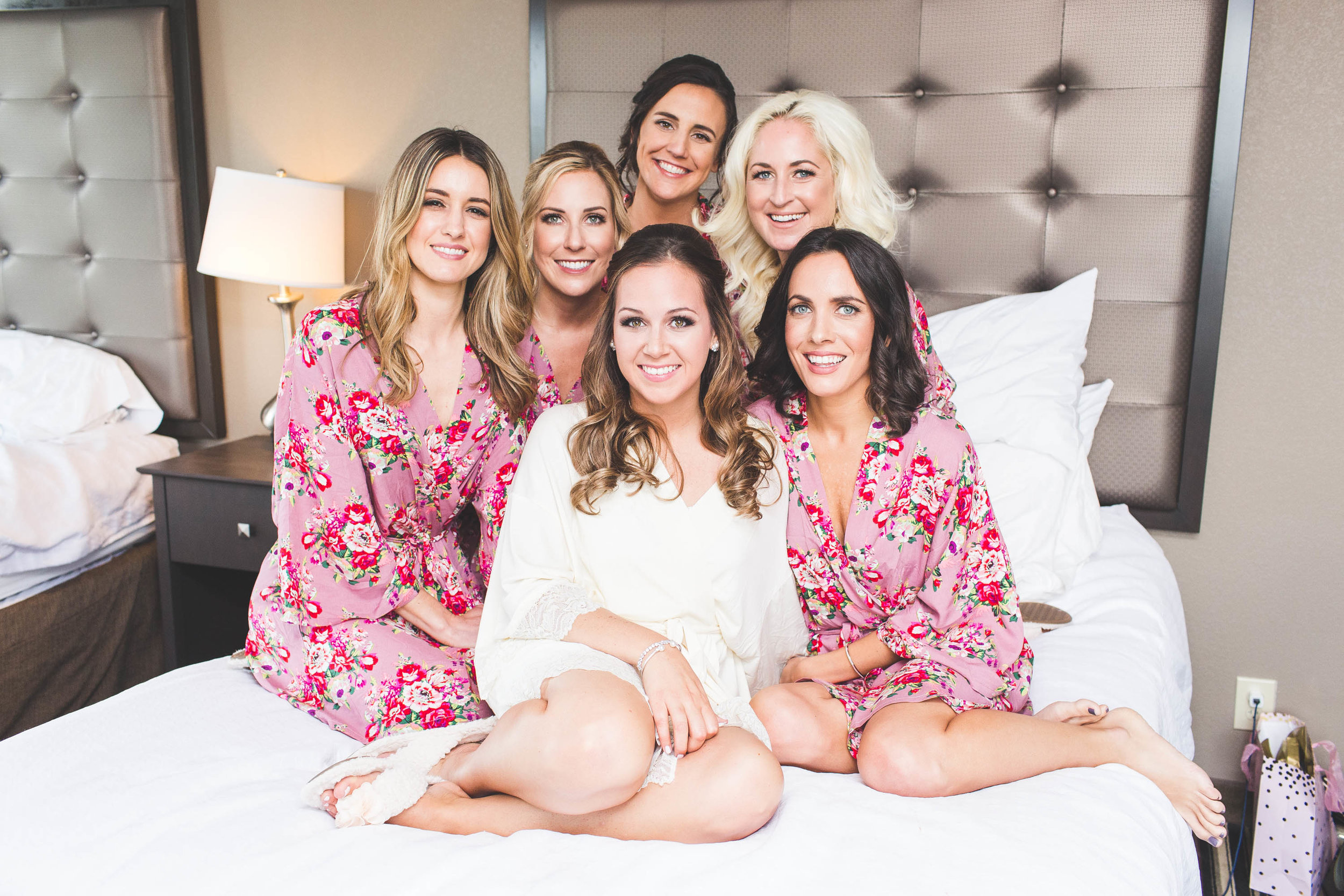 bridal party posing in floral robes on bed