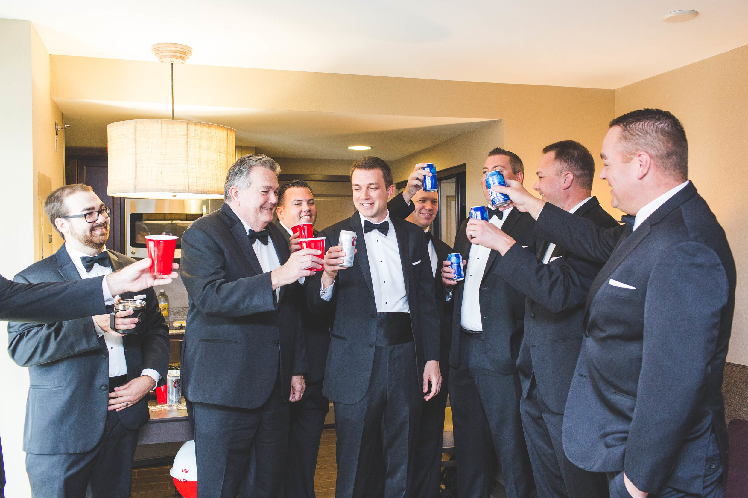 grooms party toasting to the upcoming wedding day in a hotel room