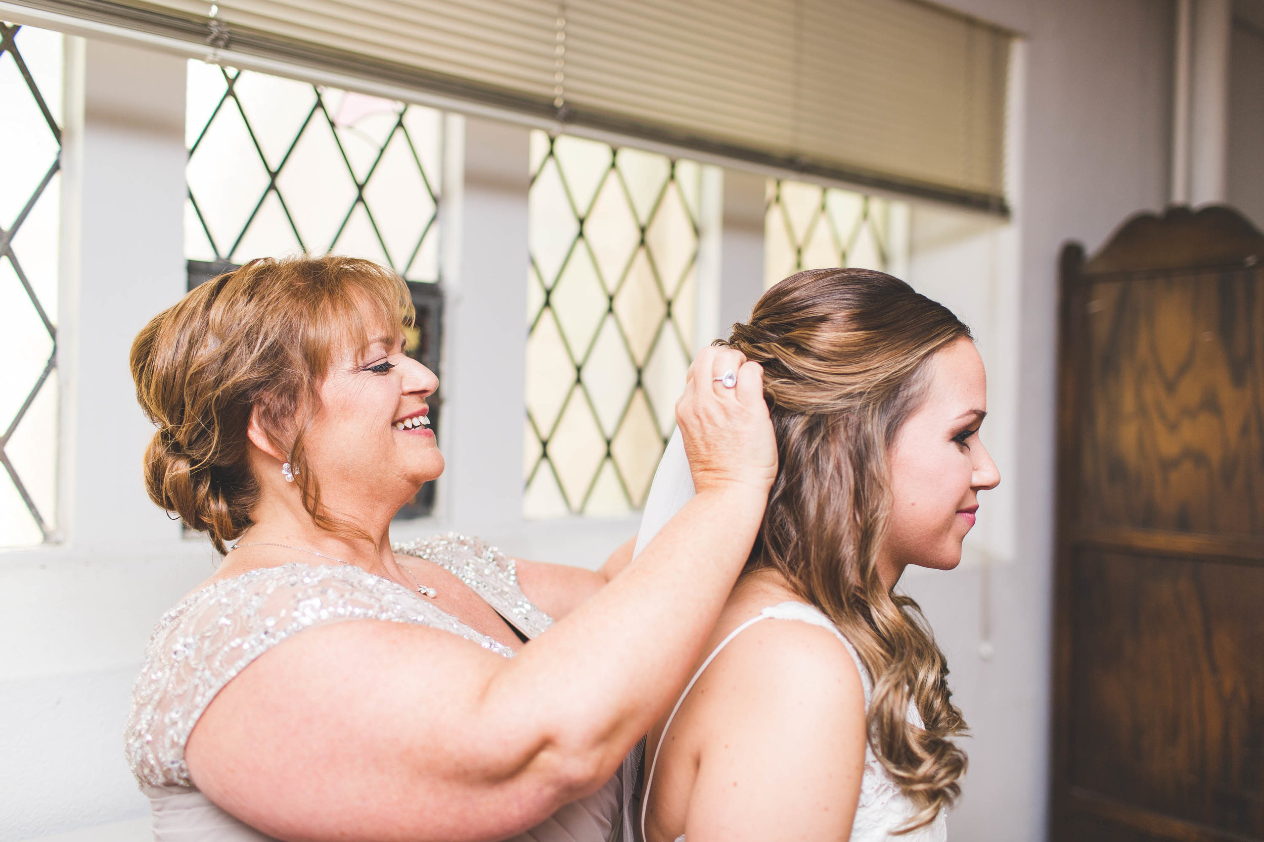 mother of bride putting on bridal veil for wedding