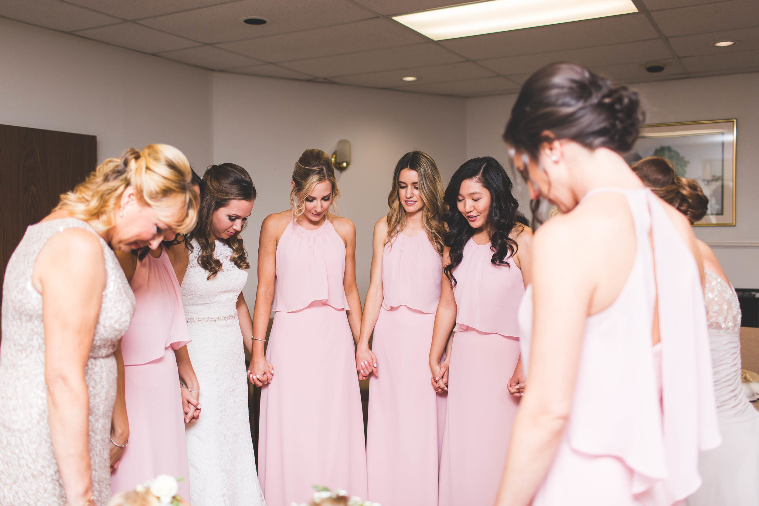 bridal party praying for bride on her wedding day