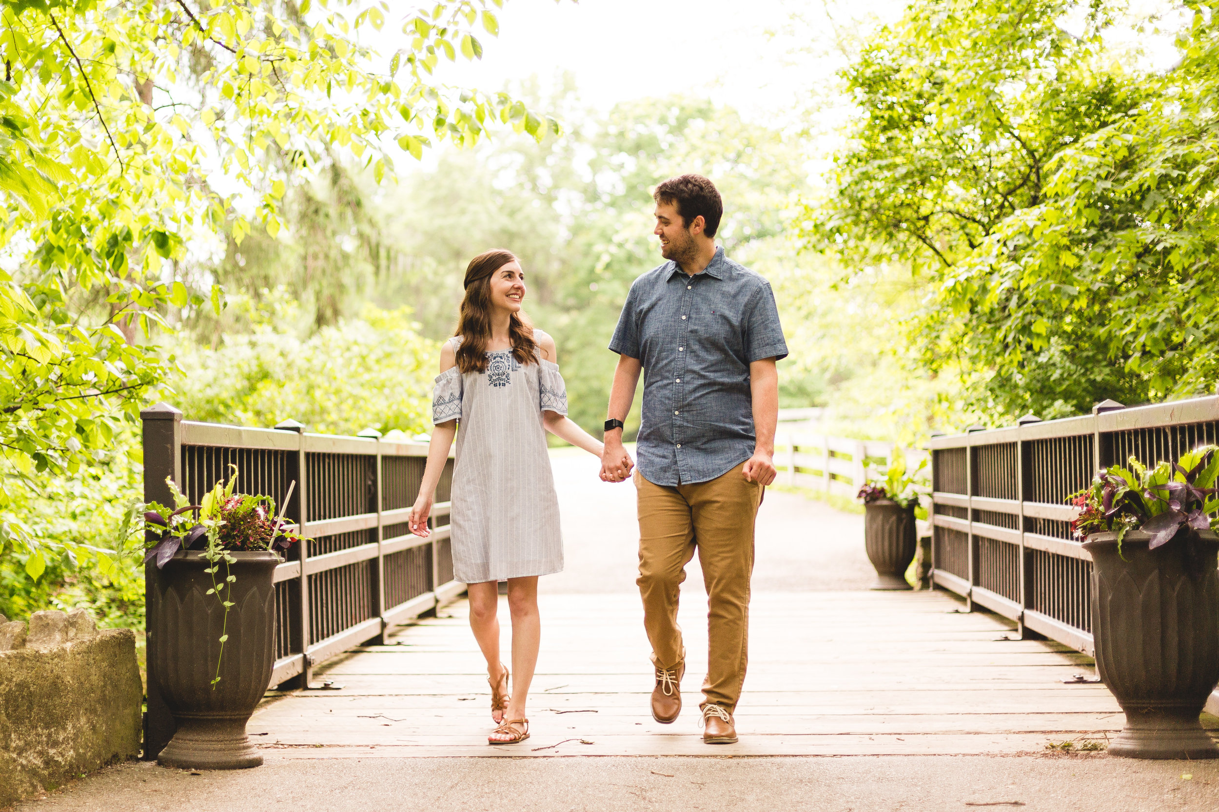 Jennifer and nate engaged walking while holding hands on a bridge in inniswood metro gardens