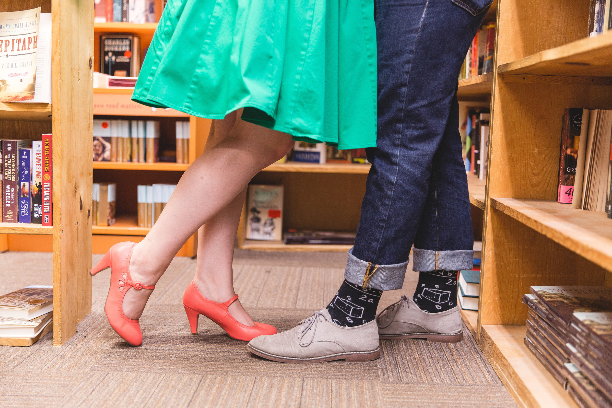 newly engaged couple show off their love for books by posing at the book loft in columbus ohio and by wearing clothing that match their personalities.
