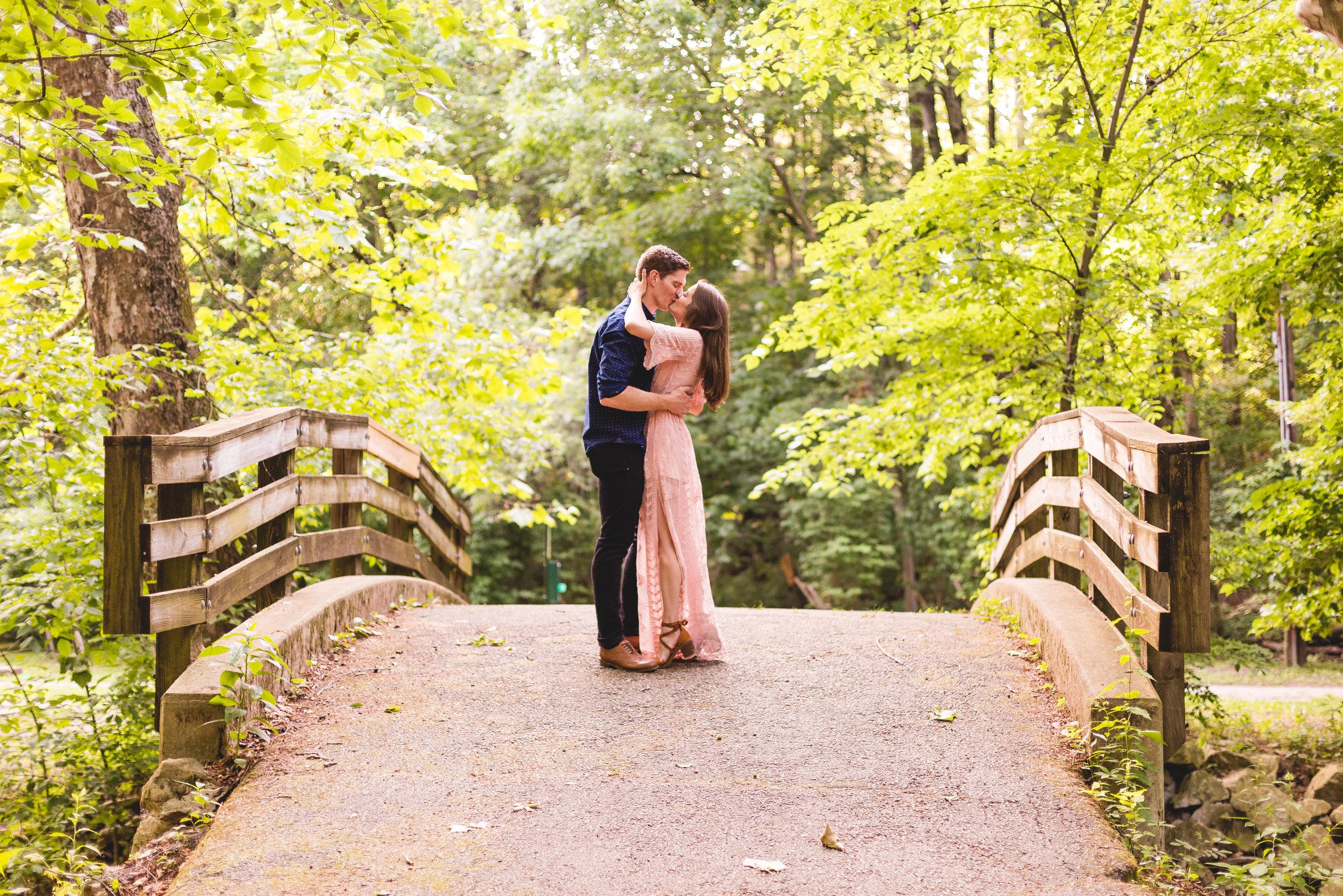 newly engaged couple kiss on a bridge at glen echo ravine Columbus ohio