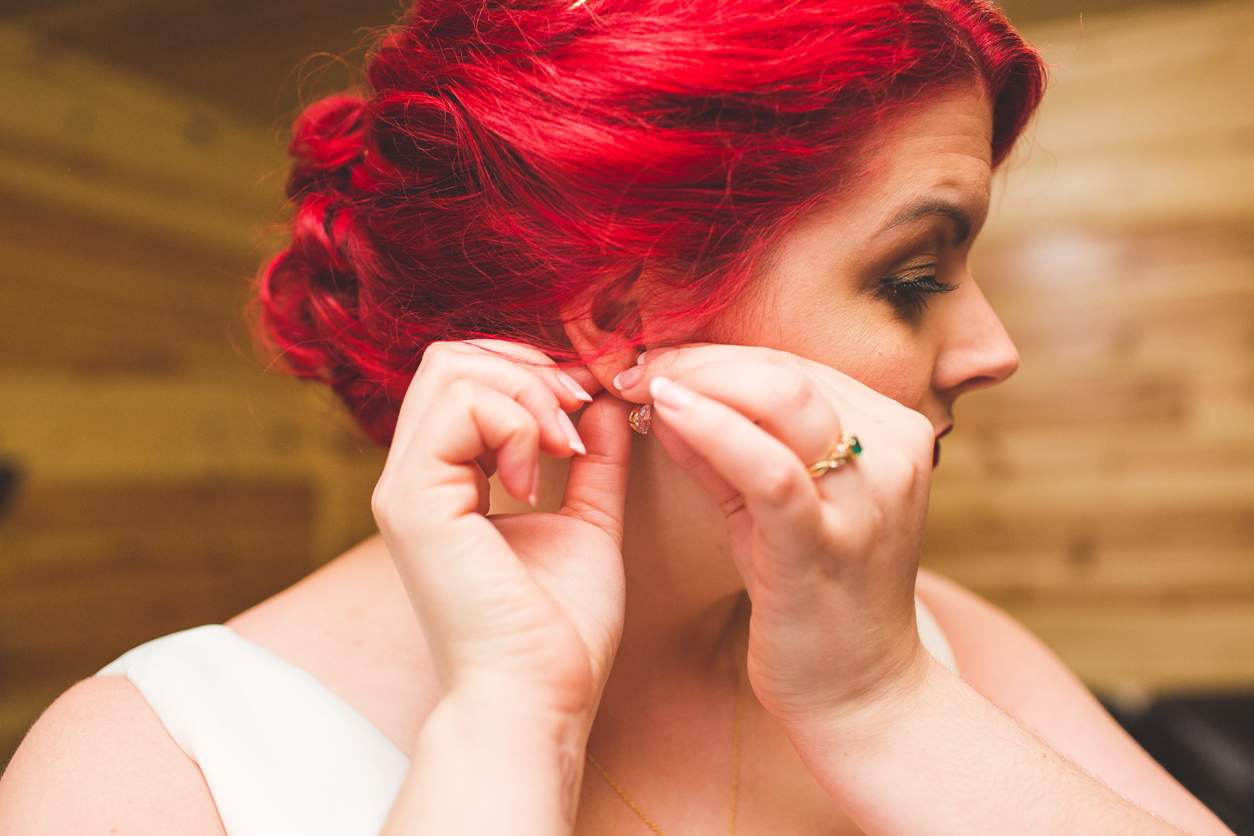 bride with red hair putting in her earrings in log cabin on wedding day in hocking hills