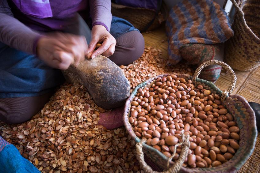 Woman shelling argan nuts in Morocco