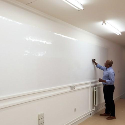 man-writing-on-glossy-surface-of-smart-whiteboard-wallpaper.jpg