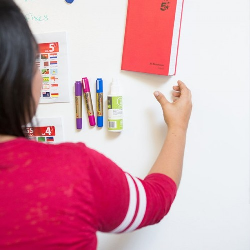 woman-hanging-up-notebook-on-magnetic-wall.jpg