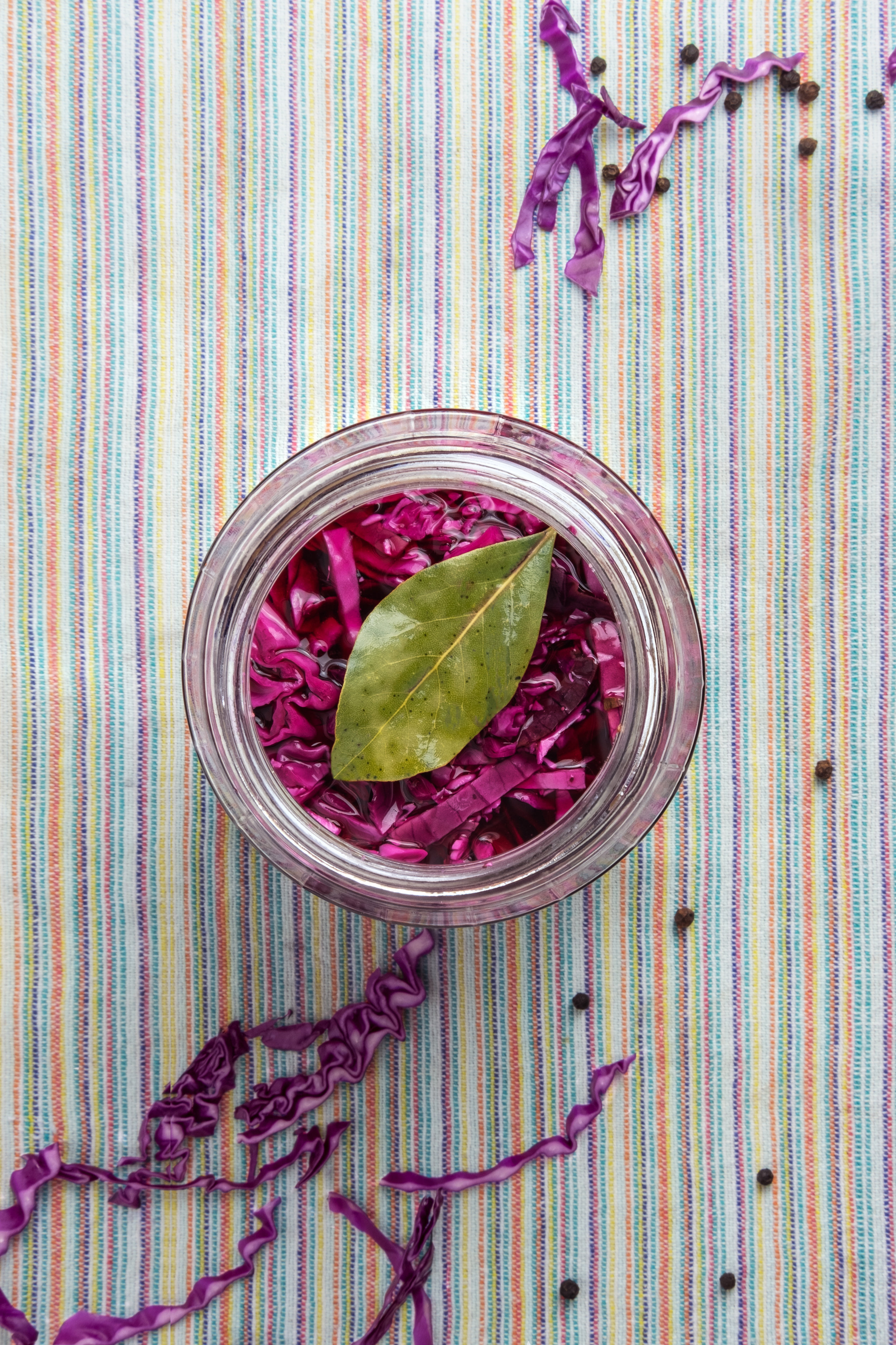 Glass jar of red pickled cabbage on a striped napkin.